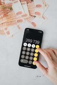 a business plan writer using a cellphone calculator